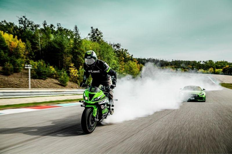 A sports bike racing a car on the track.