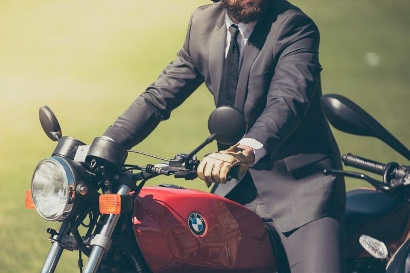 A person with a suit using a motorcycle for commuting.