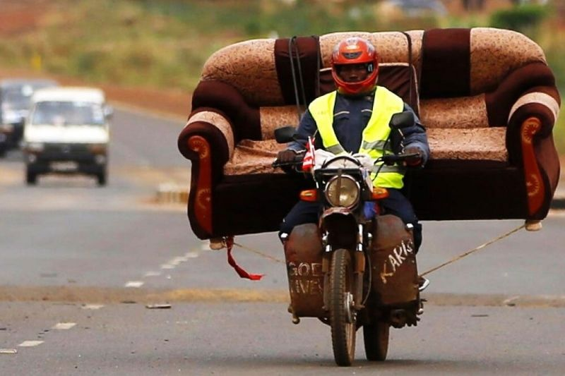 A person using a motorcycle to carry a sofa