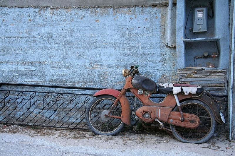 An old motorcycle that has been left sitting for a long time.