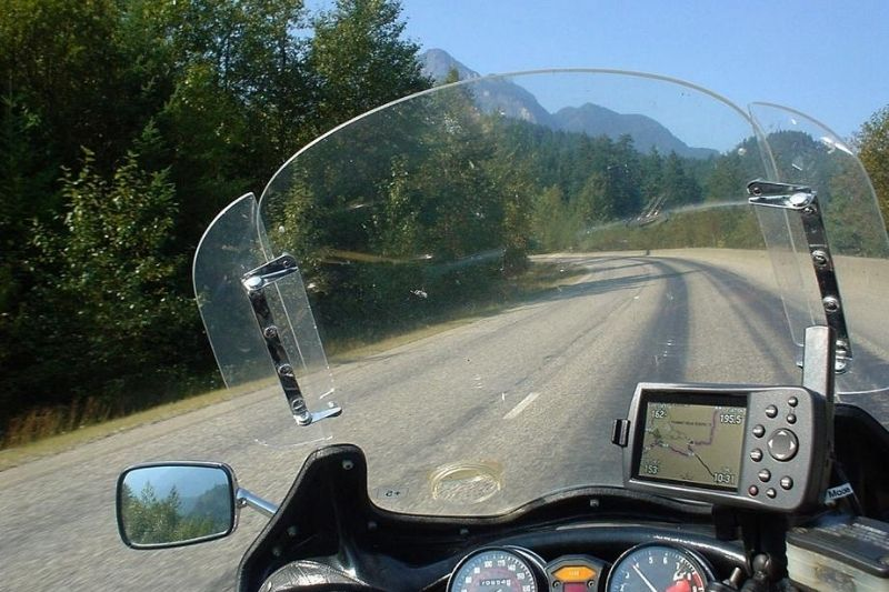 The view through the windshield of a motorcycle.