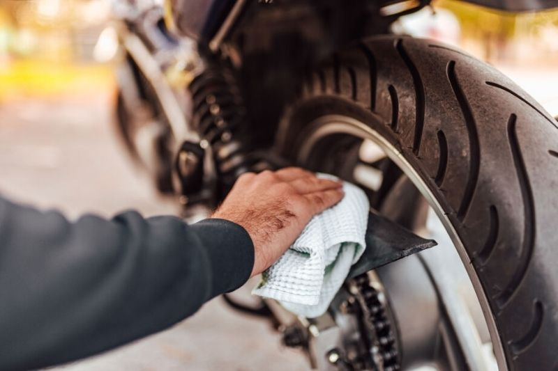 A man cleaning his motorcycle.