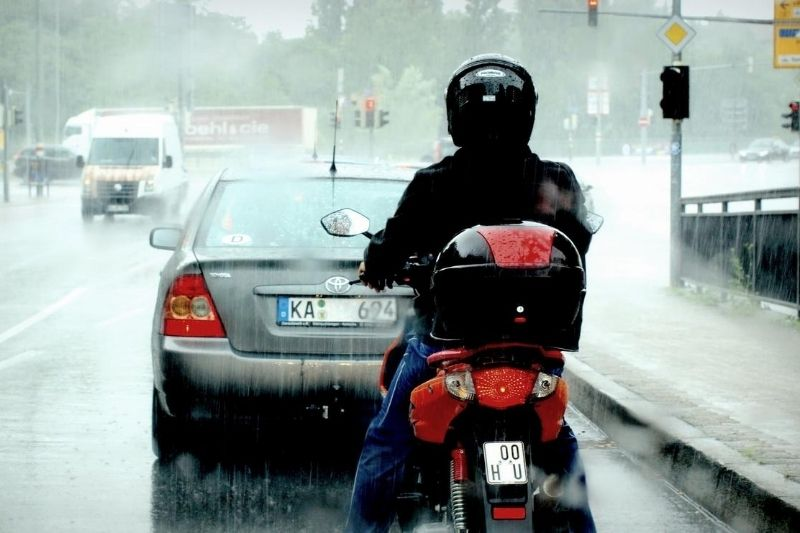 A person riding a motorcycle in the rain.