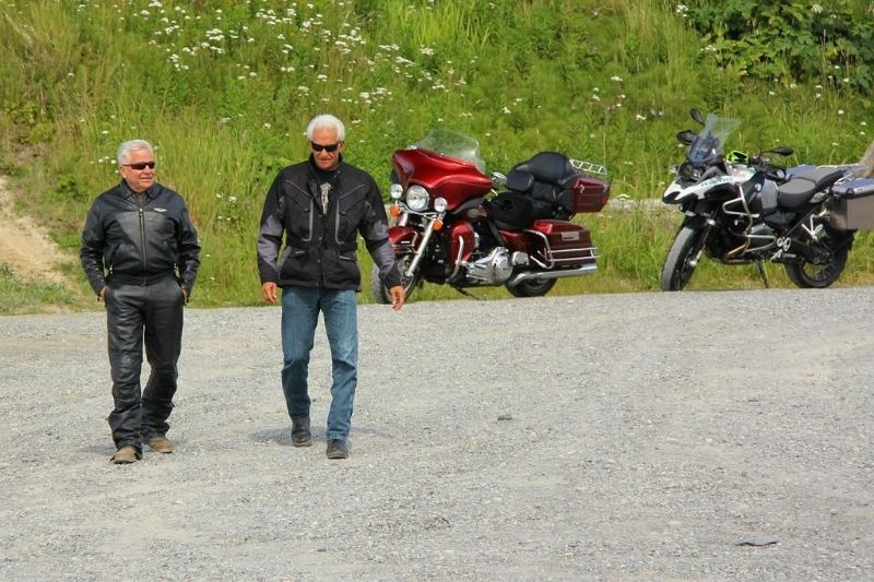 Two old motorcycle riders walking away from their motorcycles.