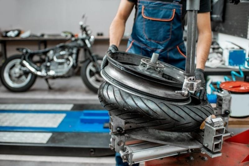 A mechanic changing a motorcycle tire