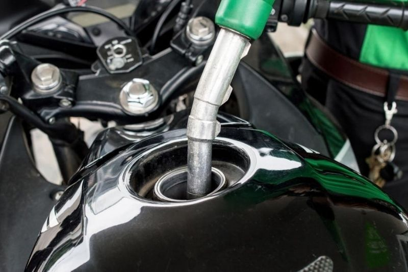 A motorcycle's fuel tank being filled up with gas.