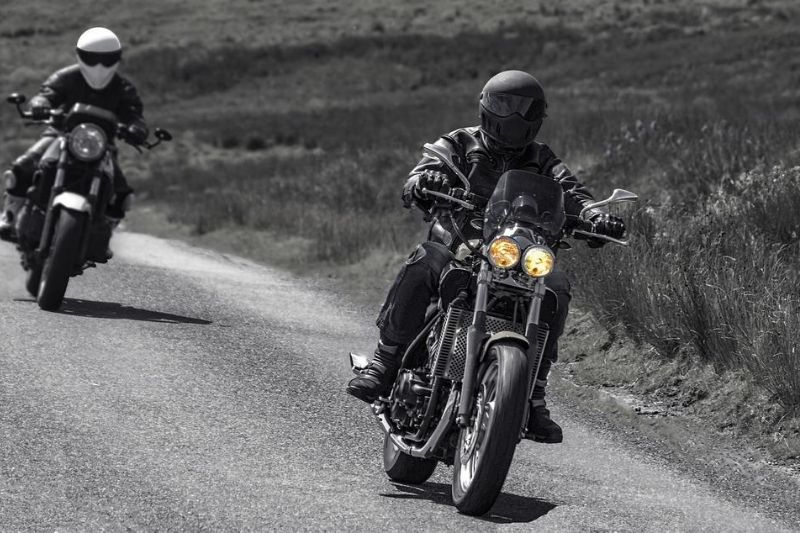 Two motorcycle riders riding in windy weather.