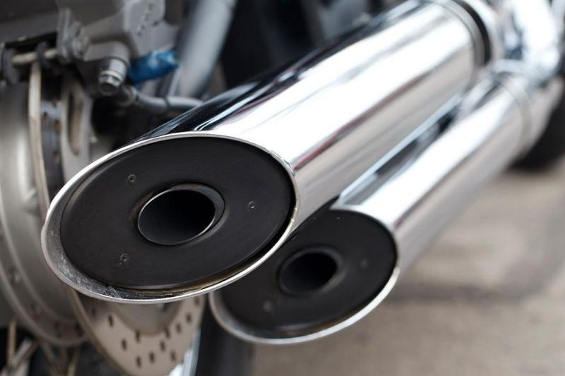 A close up of a motorcycle's exhaust pipe with baffles.