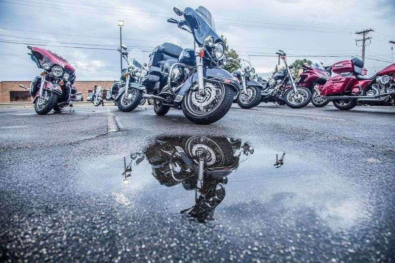 Several motorcycles that have been left sitting under the rain.
