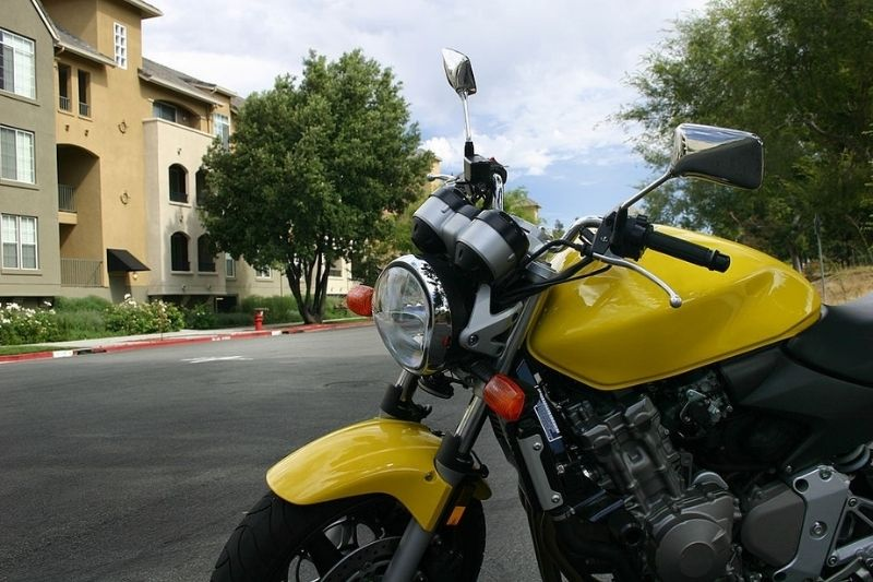 A motorcycle that is kept in a parking lot of an apartment complex.