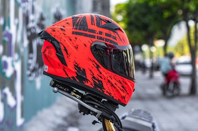 A close up of a red full face motorcycle helmet