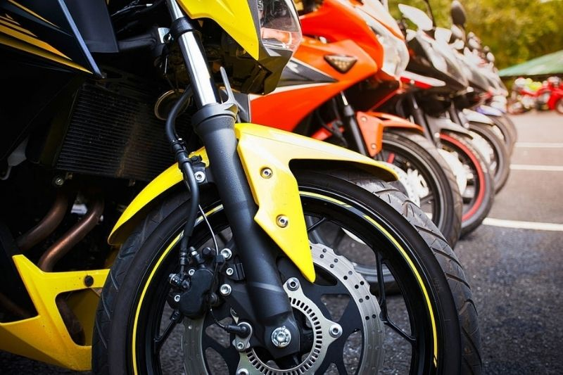 Several differently colored parked motorcycles