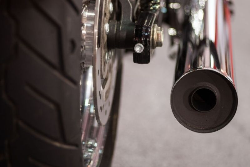 A zoom in on a motorcycle exhaust pipe with a baffle installed