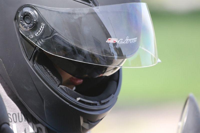 A close up of a motorcyclist wearing a helmet.