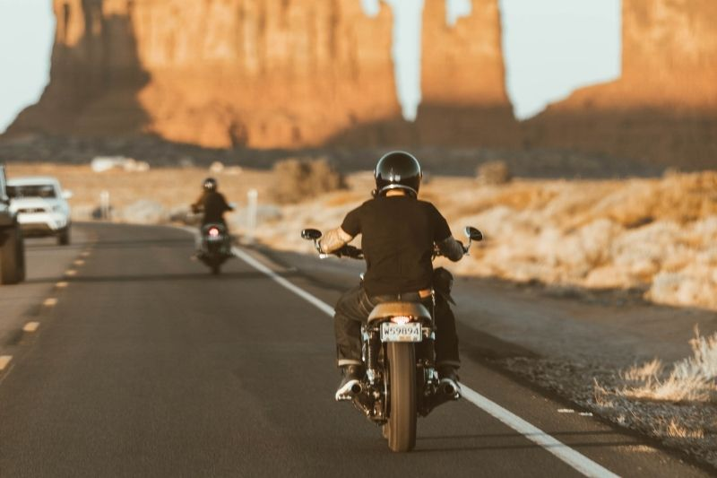 Two motorcyclists riding behind one another.